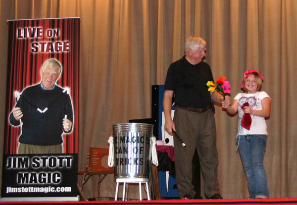 Jim Stott performing a magic trick with the help of an enthusiastic audience volunteer